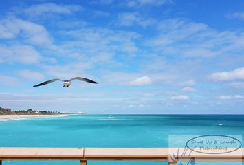 Single seagul flying over wooden bridge, above blue ocean water,  under light blue sky next to beach
