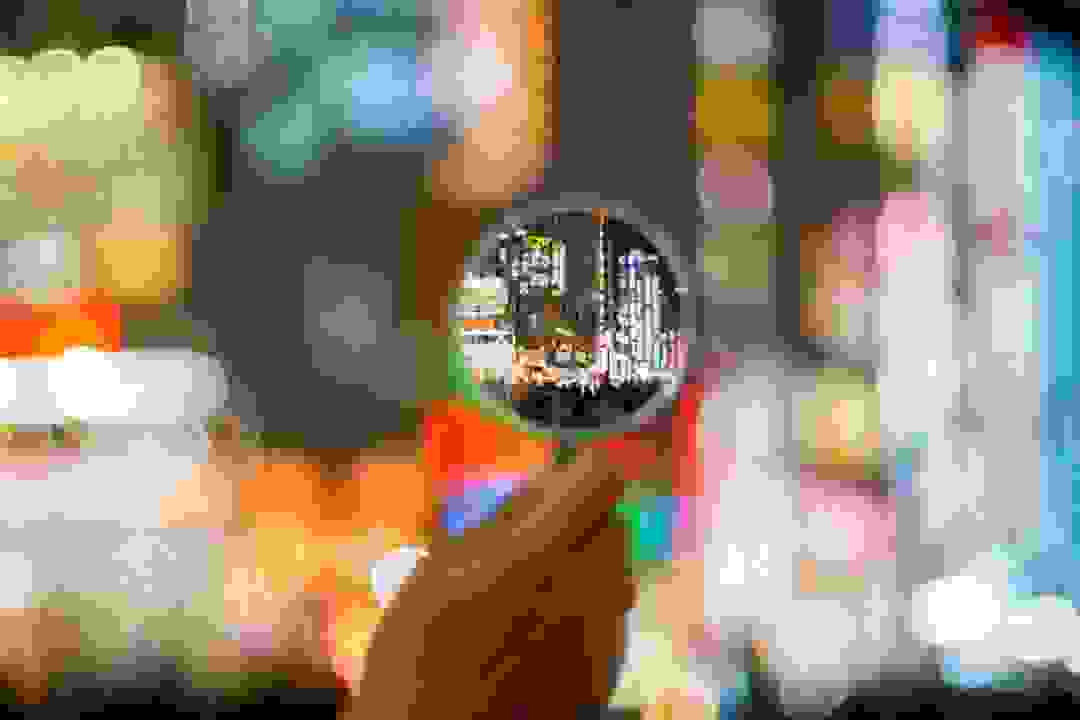 Hand holding magnifying glass in front of cityscape