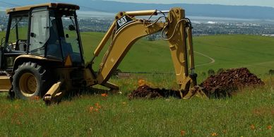 Backhoe digging a soil profile hole for septic system feasibility in Carmel Valley, CA