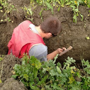 Kevin Johnston with Acorn Onsite, Inc. observing a soil profile for septic system feasibility.