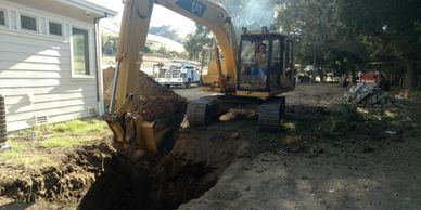 An excavator digging a septic tank hole.