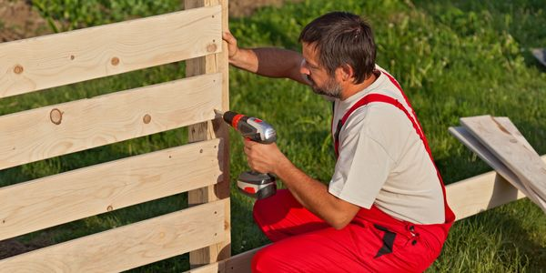 Worker placing wooden planks to make a fence