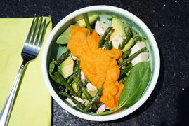 Salad bowl filled with a carrot dressing topped salad that has asparagus