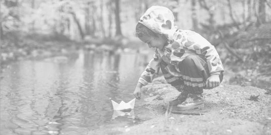 Little girl playing with paper boat, representing playful, fun adventure.