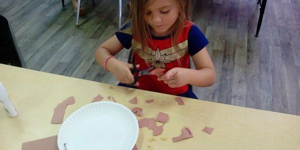 pre-k child cutting paper