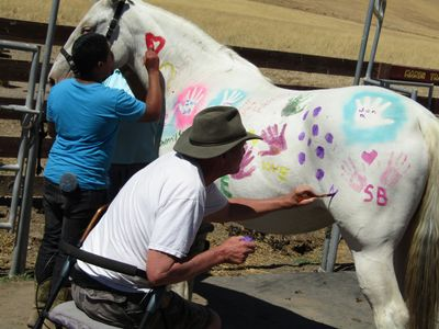 "MICHAEL MUIR AND VOLUNTEER SEAN DECORATING ""FANNY"", MOTHER OF MANY, BEFORE SHE GOES TO A NEW HOME."