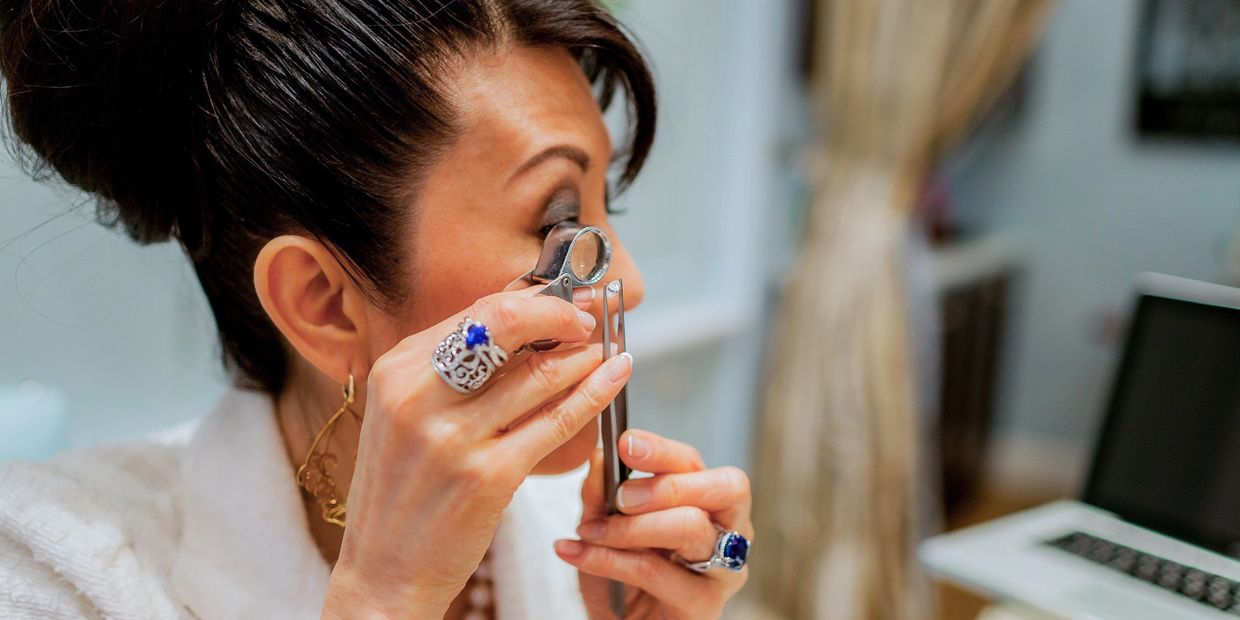 Boutique owner & proprietor Deja Laufer inspecting a loose white Diamond through a jeweler's loupe.
