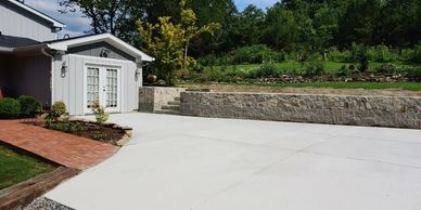 concrete driveway with retaining wall and brick walkway
