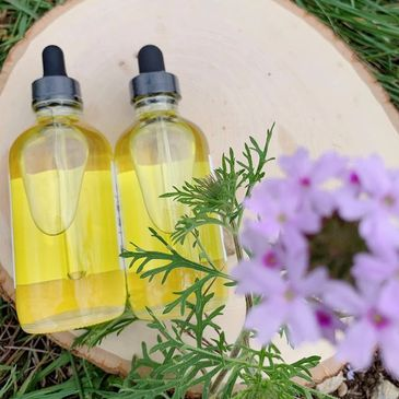 Two clear bottles of body oil sitting on a wooden tray with a green branch and a purple flower above
