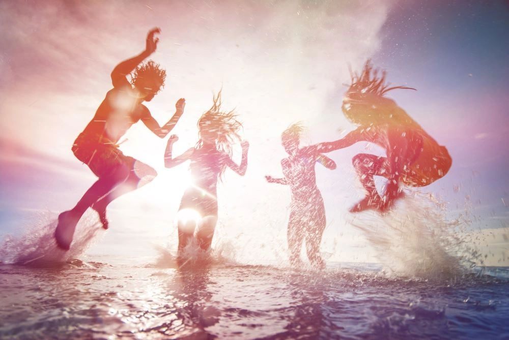 Silhouettes of people jumping in water