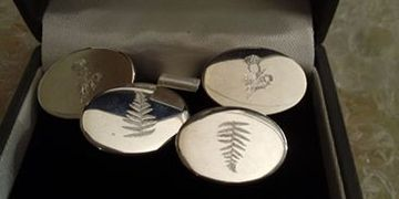 logos engraved on silver cufflinks