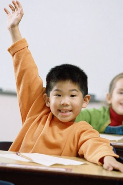 Asian young boy raising hand in a classroom.