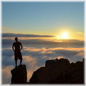 An imaginary figure of Jeff H. Ulrich standing on a high peak during the early morning light.