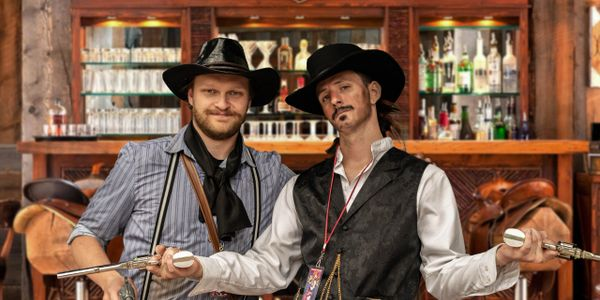 Two outlaw cowboys in front of a bar