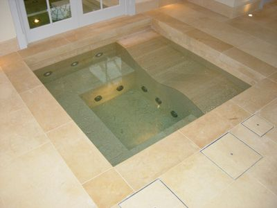 Stone clad jacuzzi spa with lounger bed. Limestone spa jacuzzi for Guncast swimming pools