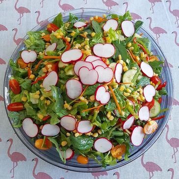Healthy garden salad with corn, radish, lettuce, rocket, spinach, capsicum, cherry tomatoes, carrot
