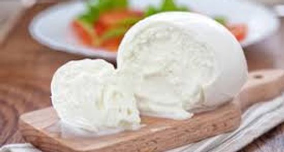 Fresh milky fior di latte mozzarella on a woody chopping board