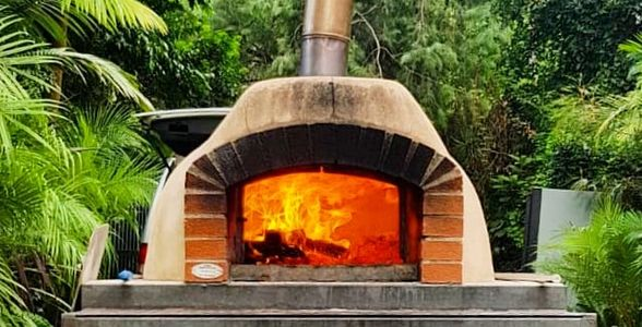 Ironbark wood burning inside a mobile pizza oven at a catering in Dural