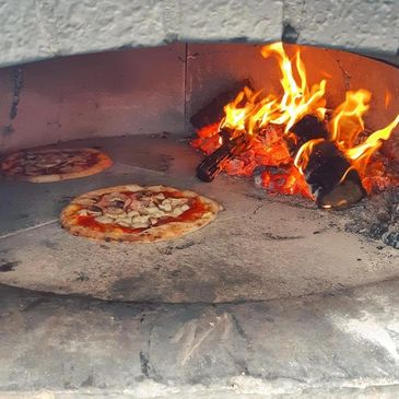 Two Ham and Mushroom pizzas cooking at a catering party inside the wood-fired oven on wheels