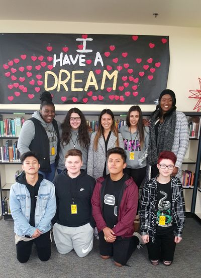 "8 student community health workers and Ophelia Noble pose in front of an ""I Have a Dream"" banner."