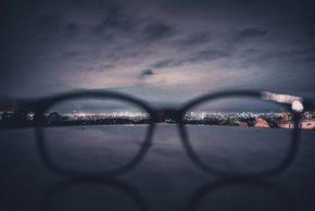 Photo looking through glasses lenses at city lights below.