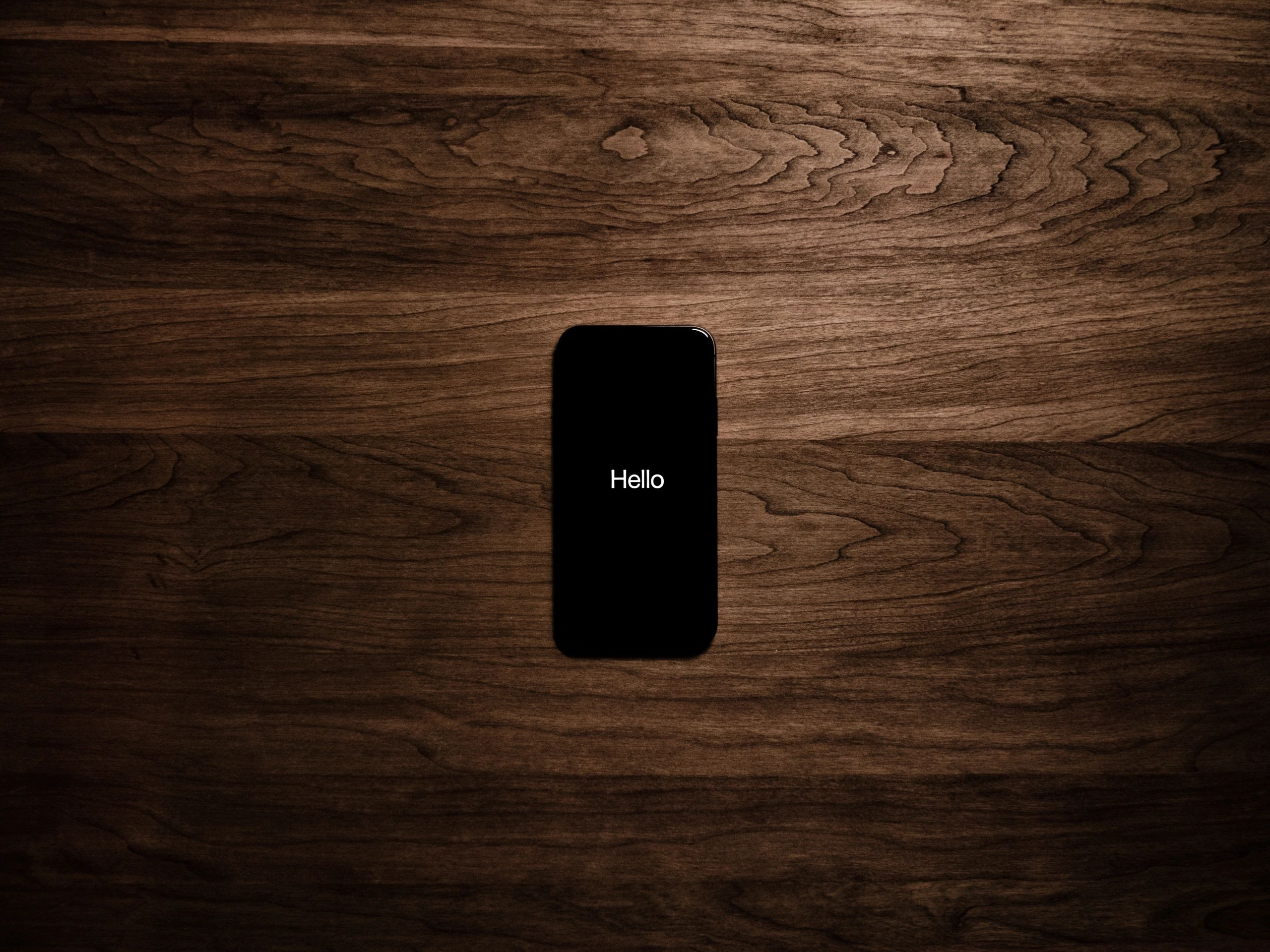 "picture of a cell phone on a wooden background. The cell phone screen says ""Hello"""