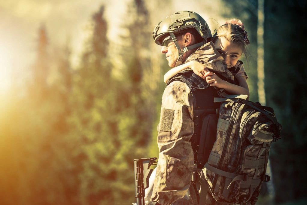 Soldier holding young girl