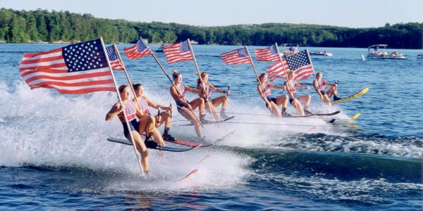 Water-skiers holding American flags at the Min-Aqua Bats Ski Show