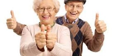 Happy smiling elderly couple giving two thumbs up sign.