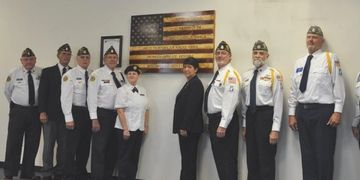 Honor committee proudly standing under the new American Flag.