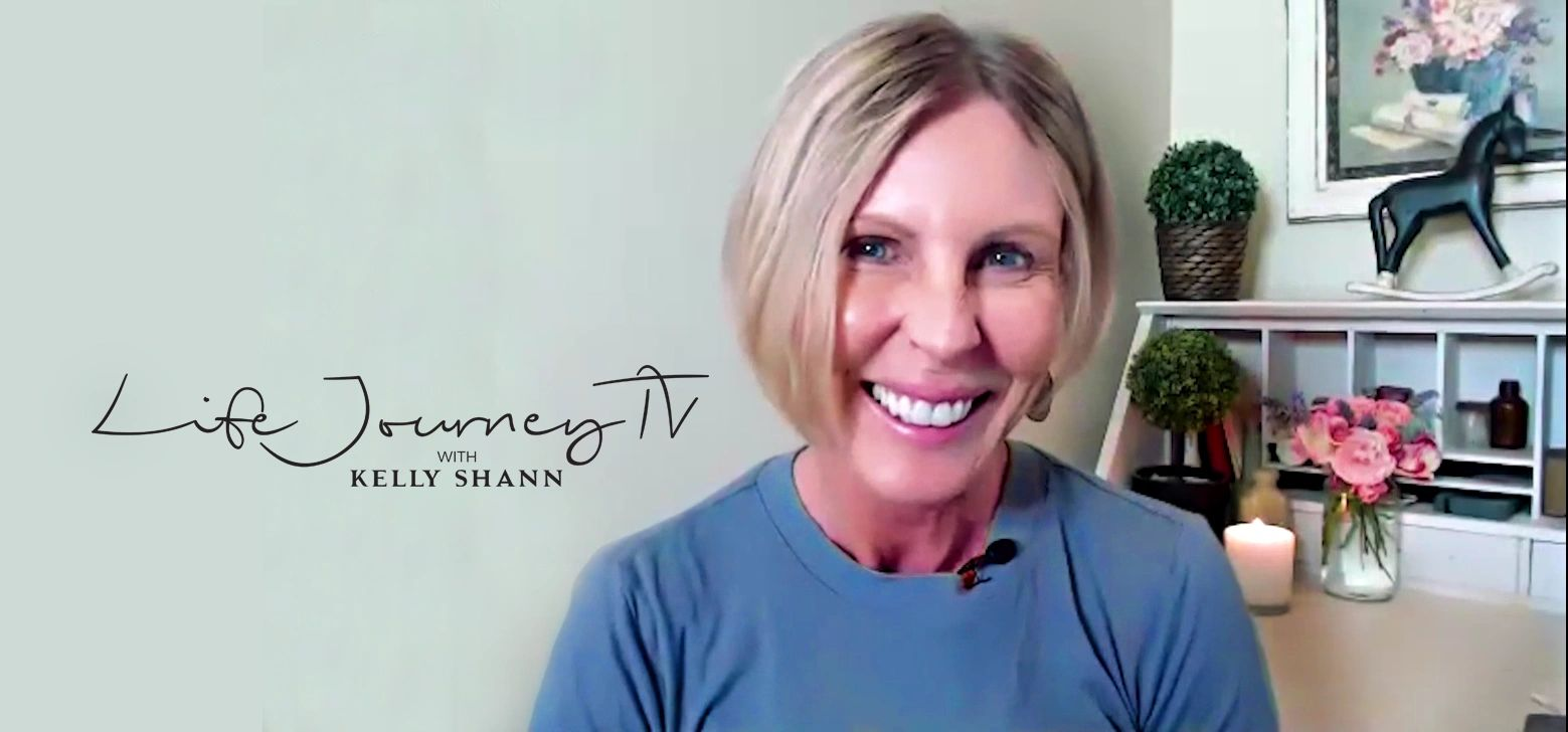Kelly Shann sitting at desk with Life Journey TV logo in the background