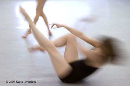 A dancer in motion extends her leg and arms. A second dancer's legs are seen in the background.