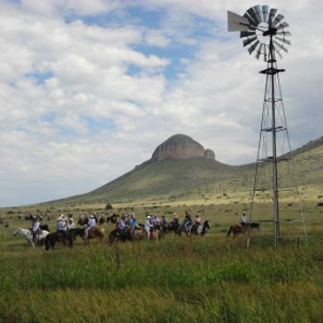 Windmill and horseback riders with biscuit hill in the background