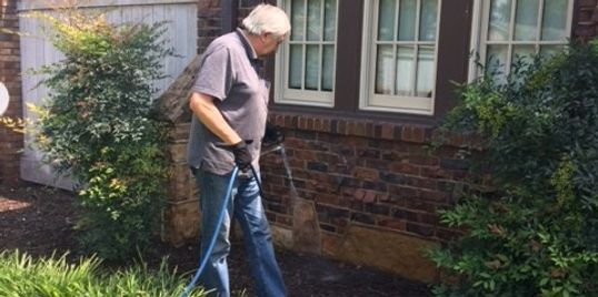 Picture of Jim spraying an exterior property