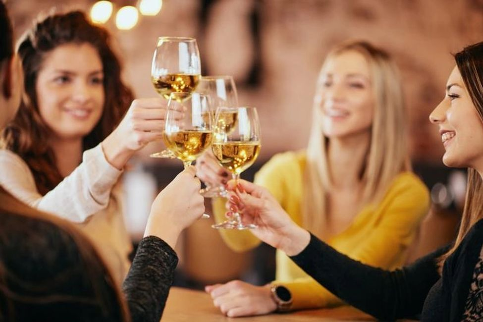 Group of girlfriends clinking wine glasses