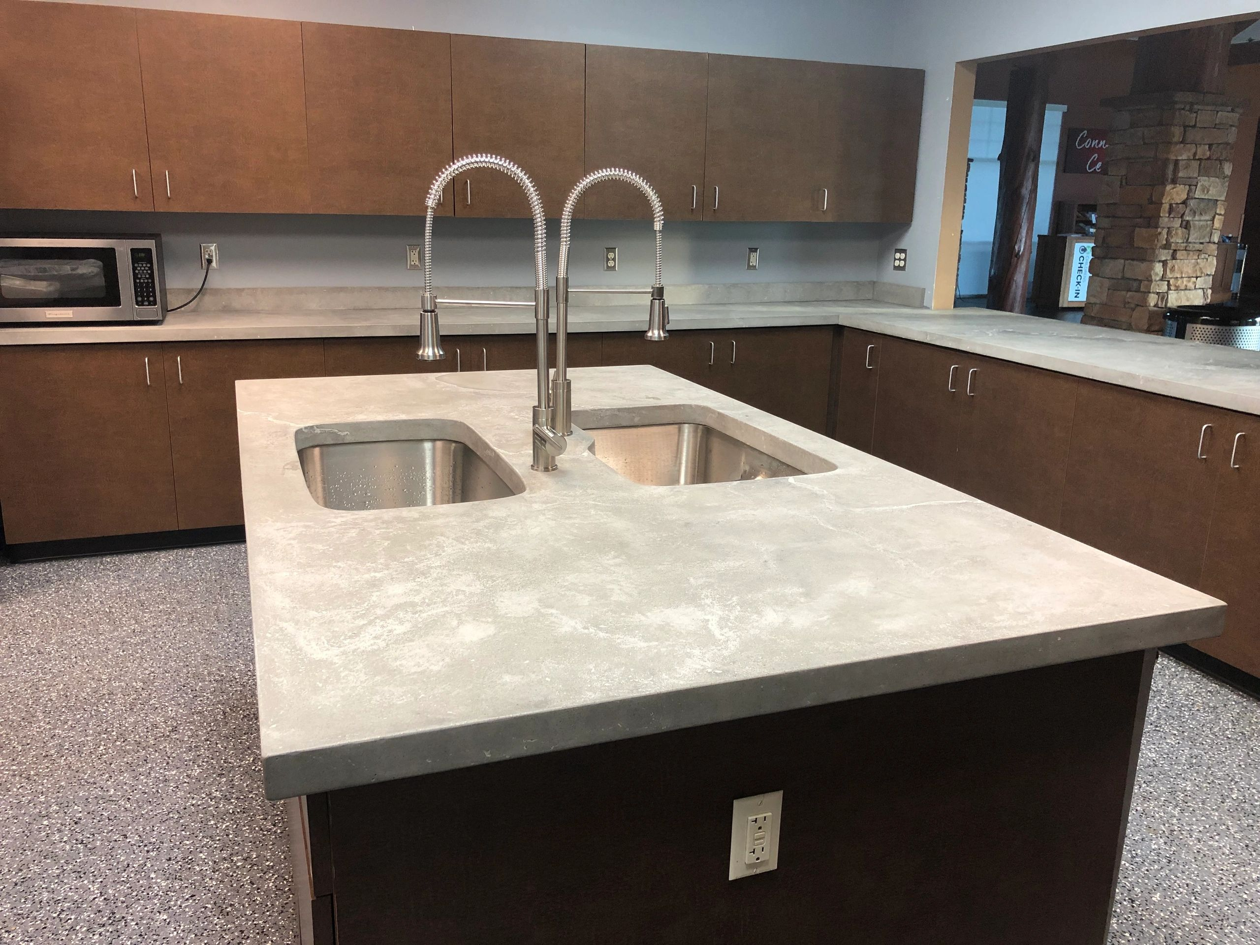 Concrete countertops in natural gray with black and white veining.