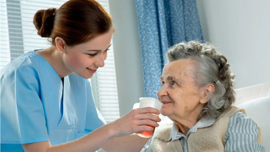 Caregiver helping elderly family member drink from a cup.