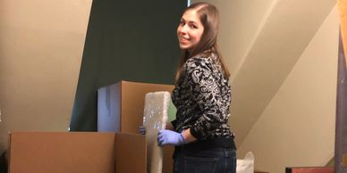 Woman packing a wrapped frame into a box