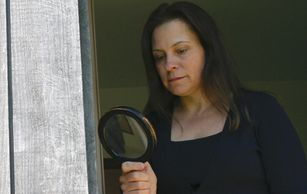 Woman using magnifying glass to examine a door