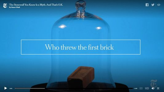 "NY Times' screenshot from video ""Who Threw the First Brick?"". The image  is of a brick under glass."