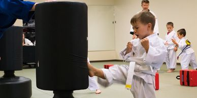 A Tiny Champion kicking a karate pad while his instructors watch. Best little martial artist ever!