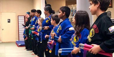 A group of our karate kids in the family class holding their nunchaku while they wait for instruction from their black belt instructors.