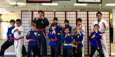 A bunch of our karate kids posing for a photo after completing their martial arts belt test.