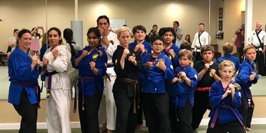 a group of our family class students posing with their best karate stance after successfully completing their martial arts belt test.