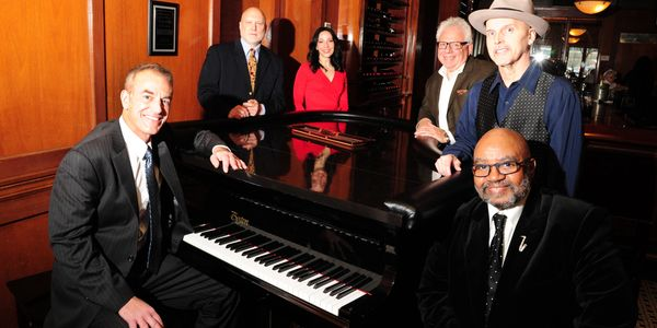The Mike Petrone Band posing in front of a shiny piano in an oak room.