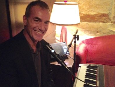 Mike Petrone smiling at the microphone and sitting in front of portable keyboard.