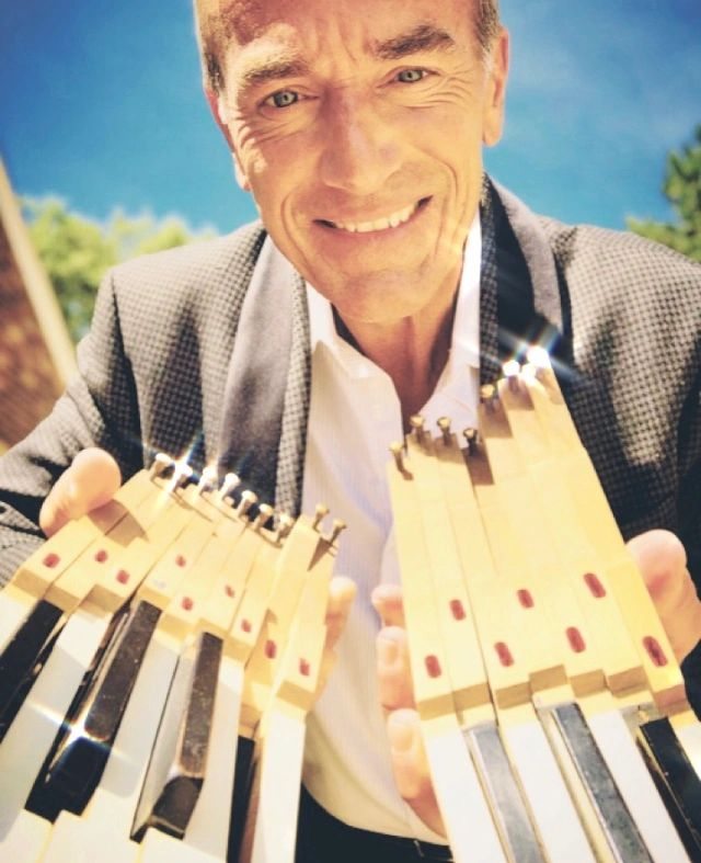 Mike Petrone smiling and holding two sets of detached piano keys on a sunny day.