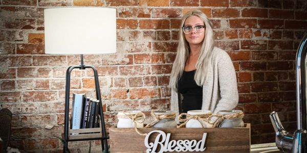 Ashlyn Miller overlooking one of her finished wood cubbies with decorated mason jars.