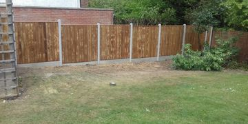 Close boarded panel fencing with concrete post and concrete gravel boards