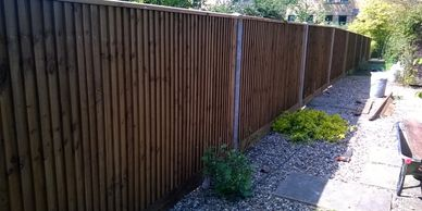 Close boarded fencing with concrete post and wooden gravel boards